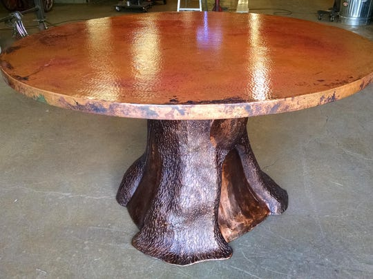 A circle of copper defines this tree trunk dining table.