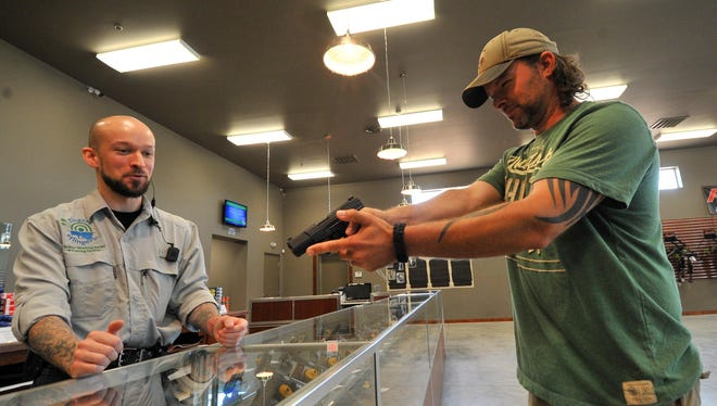 Customer Marty Cheyka, right, of Wausau, does an eye sight aim on a pistol while worker Ty Baker, of Merrill, looks on Friday afternoon at Zingers & Flingers indoor shooting range in Wausau.