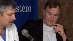 Former President George Bush, right, listens to cardiologist