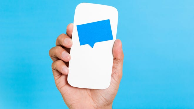 Hand showing a paper smartphone concept with blue speech bubble, chat, notifications or message incoming. All this on vibrant blue background.