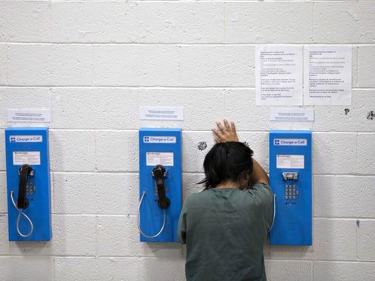 Una mujer hace una llamada dentro del Centro de Detención