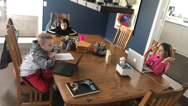 From left, Max Dooley, Isa Dooley, and Mia Dooley, all age 9, do their schoolwork at home after schools shut down March 16.