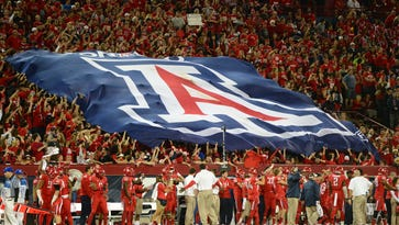 Wildcats fans hold a flag in the grandstands in the second half of a game against rival ASU on Nov. 23, 2012, at Arizona Stadium.