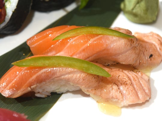 The torched salmon, a two-piece Super Happy nigiri, is made with green bell pepper and a pineapple-mirin glaze.