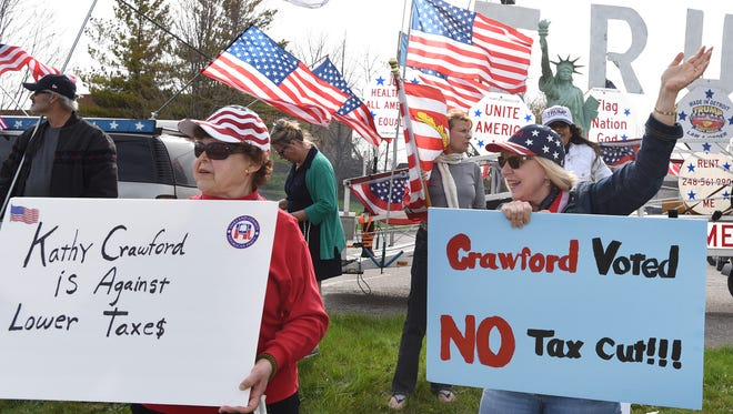 Marlene Palicz (left) and Marge Mancuso, of Walled Lake and Commerce Township protest at the Novi Post Office on April 17 against 12 Michigan Republicans who voted against a small tax cut. One legislator being protested was Novi's Kathy Crawford.