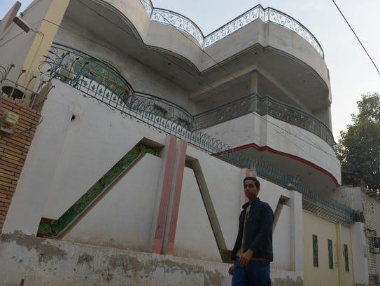 A  resident walks past the house of Gulzar Ahmed Malik,