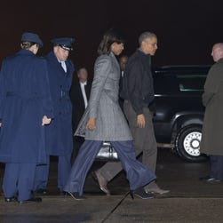 President Obama and first lady Michelle Obama  board Air Force One for New Delhi on Saturday night.