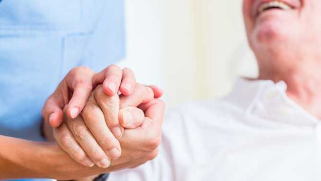 A nursing assistant holds the hand of an elderly man.