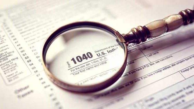 A magnifying glass sits on top of a 1040 tax form.