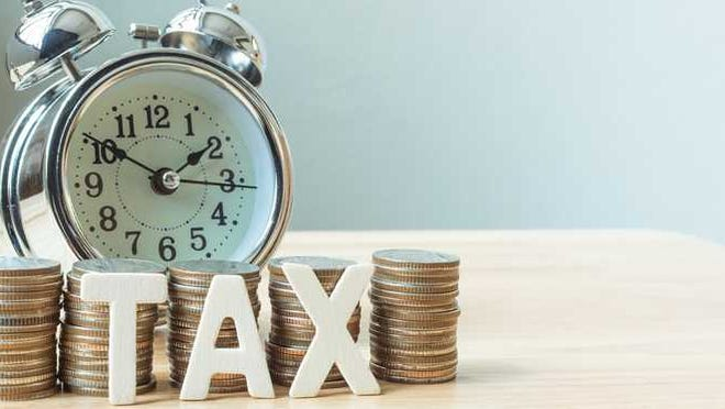 The word tax sits in front of stacks of coins and an alarm clock.