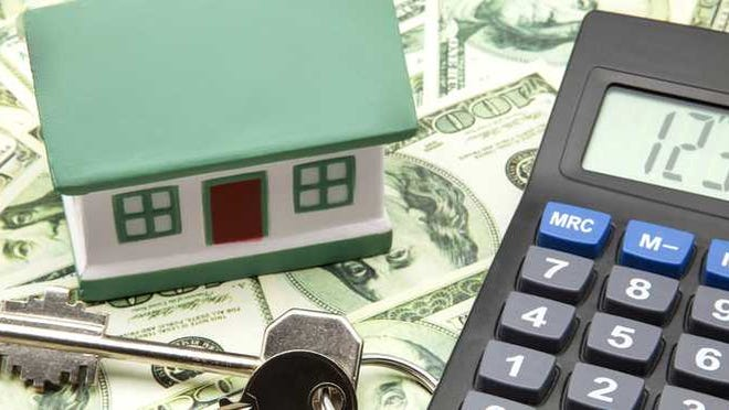 A house figurine next to keys and calculator on top of money.