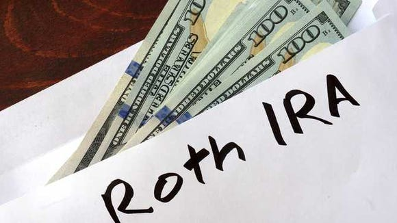 Envelope labeled ROTH IRA filled with cash.