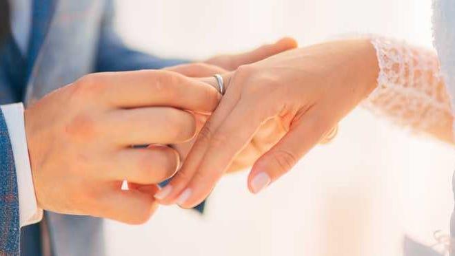 Man slips wedding ring onto bride's finger.