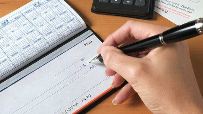 Pen in hand above blank check.