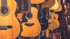 Rows of guitars in a guitar shop.