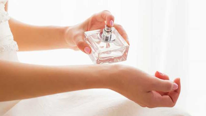Woman sprays perfume on her wrist.