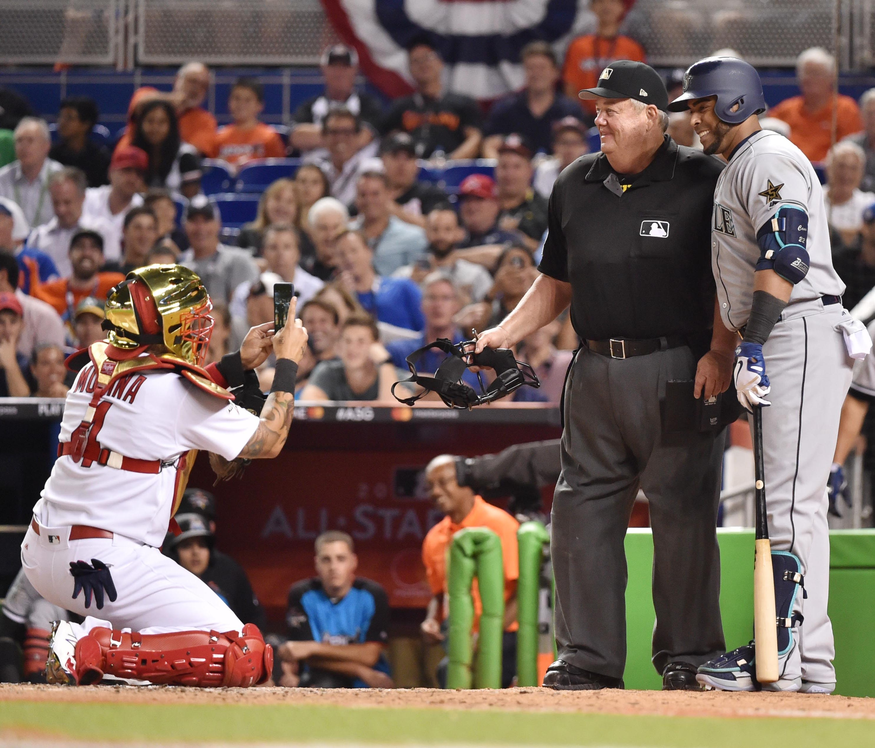 Yadier Molina takes a photo of Nelson Cruz with umpire Joe West in the sixth inning of the All-Star Game.