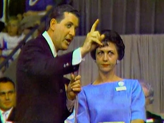 Host Monty Hall, left, talks to a contestant on an