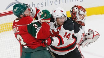 New Jersey Devils goalie Cory Schneider, right, watches play as teammate Adam Henrique tries to keep Minnesota Wild's Charlie Coyle contained during Tuesday's game.