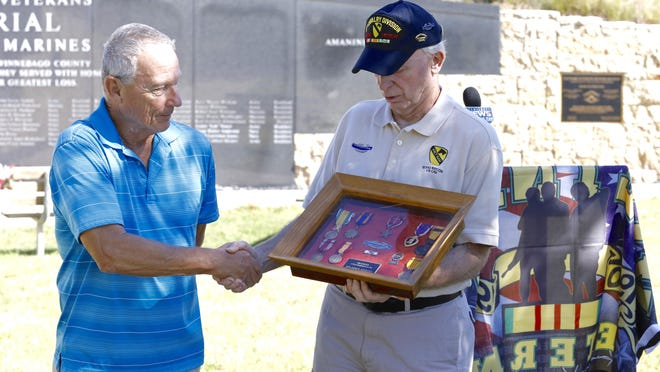 Mike Trisch, left, 72, of Belvidere, shakes hands with Charles Allan Larson after Trisch donates John Roger Hornsby's Vietnam War medals to the Vietnam Veterans Honor Society on Wednesday at the LZ Peace Memorial in Rockford. Trisch's late wife was married to Hornsby before he died in March 1969.