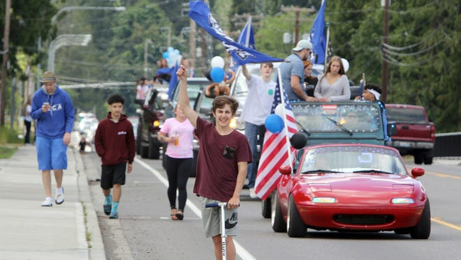 """Trevor Brown, on a scooter, leads North Mason's graduating seniors on their annual """"Slow Day"""" parade through Belfair on Monday."""
