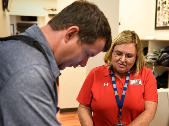 Tammy Bass helps Army veteran Charles Wall check into the USO lounge at the Nashville International Airport Friday, Sept. 8, 2017 in Nashville, Tenn. Bass is a mother of a former soldier who was killed in action. He signed up to serve after 9/11, and now she's dedicating her life to those who serve.