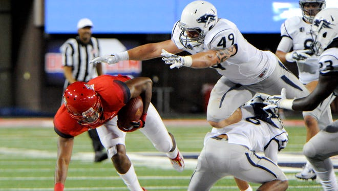 Wolf Pack linebacker Jordan Dobrich leaps to tackle Wildcats receiver Cayleb Jones during their game last season.