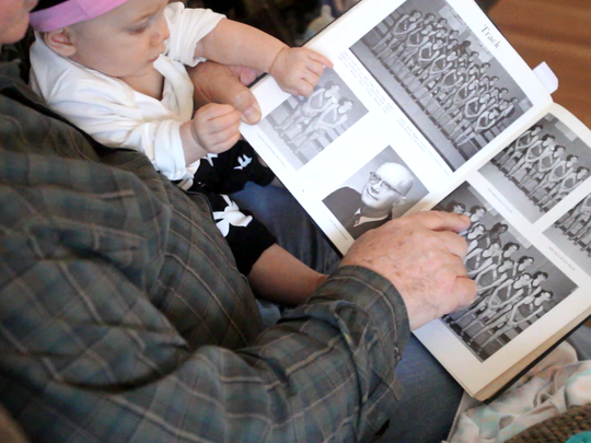 Randy Rubel looks at his class  of '67 yearbook from Clarksville High School with his great-granddaughter in January 2017. Some of his good friends were students from the all-black scjool.