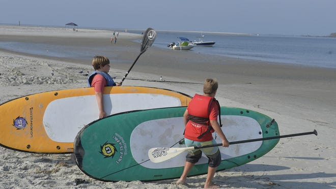 A couple of campers carry their paddle boards to Tybee Creek  Wednesday.