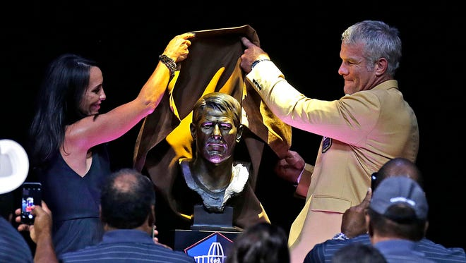Aug 6, 2016; Canton, OH, USA; Former Green Bay Packers quarterback Brett Favre is introduced by his wife Deanna Favre (left) as his bust is unveiled  during the 2016 NFL Hall of Fame enshrinement at Tom Benson Hall of Fame Stadium.