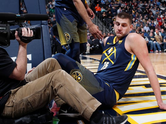 Denver Nuggets center Nikola Jokic, back, reacts after drawing his second foul and tumbling into cameraman Kevin White during the first half of the team's NBA basketball game against the Los Angeles Clippers Tuesday, Feb. 27, 2018, in Denver. (AP Photo/David Zalubowski)