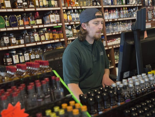 Trever Craig works the front counter at Bullfrog Wine