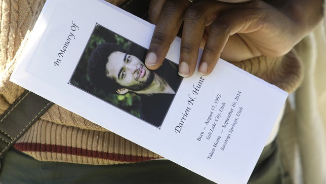 A family friend holds the funeral program for Darrien Hunt following his funeral Sept. 18, 2014, in Saratoga Springs, Utah.