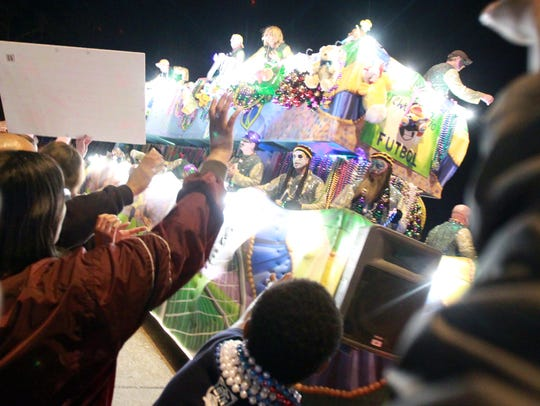 Revelers cheer and grab for beads as a float passes