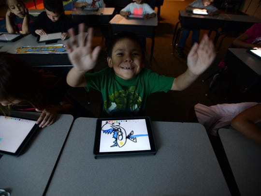 Itay Small Boy Jr. and his classmates in the Box Elder School kindergartner class use their new iPads on Tuesday morning. Box Elder was one of three Montana schools selected for Apple's ConnectED Grant; receiving approximately $1.8 million in time and supplies, which included 460 iPad tablets for students as well as laptops for faculty and technological support and upgrades to the school.