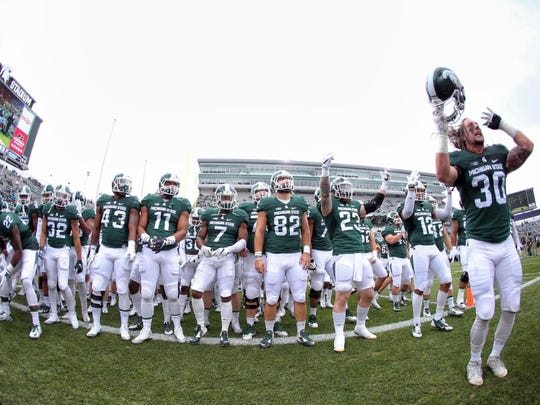 Linebacker Riley Bullough leads the Spartans onto the field before last Saturday's game against the Northwestern Wildcats at Spartan Stadium. Michigan State lost, 54-40, and fell to 2-4 overall and 0-3 in the Big Ten. The Spartans have played in a bowl game the past nine seasons, including last season's College Football Playoff.