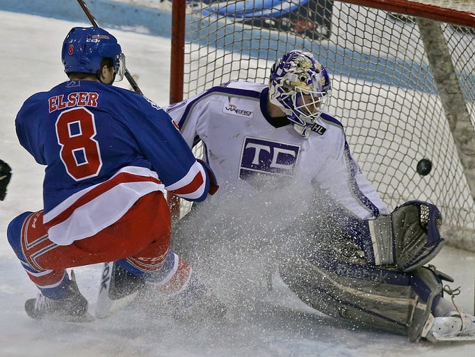 Des Moines Buccaneers' #8 Danny Elser watched the puck fly into the net as he scored his team's second goal and his second goal of the first period against Tri - City Storm goalie #41 Hayden Lavigne in the final home game of the season on Friday night April 4, 2014.