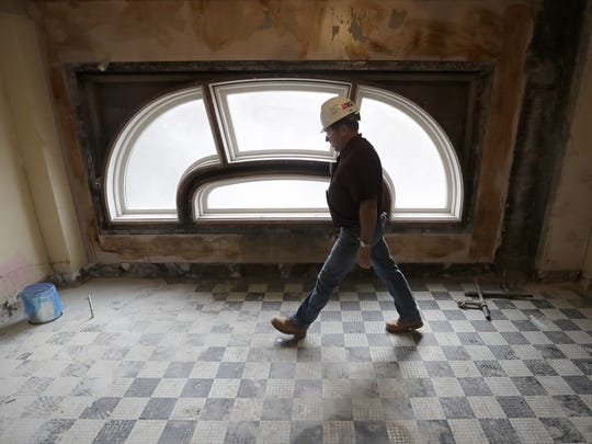 Bob Verzal, the on-site supervisor of the Hotel Northland restoration, walks past an original window that was uncovered in the mezzanine-level ladies room.