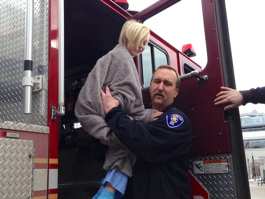 Jacob Hutchins of Burlington gets a lift from Assistant Fire Marshal Michael J. Charney after checking out a Burlington Fire Department truck.