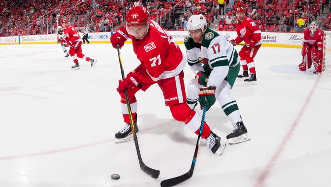 Detroit center Dylan Larkin and Minnesota left wing Marcus Foligno battle for the puck in the second period Thursday night.