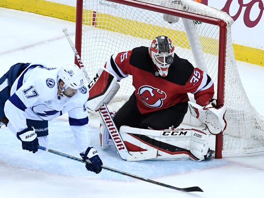 The puck sails by New Jersey Devils goaltender Cory