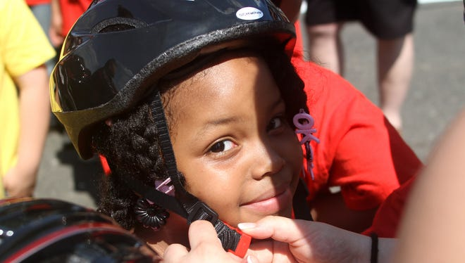Old Bridge, NJ - Seven-year-old Jaimielis DeLeon of Red Bank gets some help with her helmet, Sunday, June 2, 2013, prior to riding her new bike at the start of the NHRA Summernationals at Old Bridge Township Raceway Park.