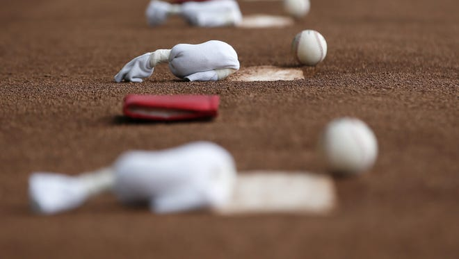 Rosin bags and baseballs line pitching mounds during Cincinnati Reds spring training, Thursday, Feb. 18, 2016, in Goodyear, Arizona.