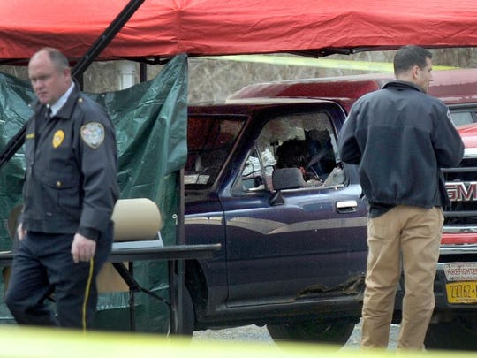 In this April 12, 2018, photo, police work at the scene where a man and a woman were found slain in a pickup truck in Gaylordsville, Conn. Police say Steven Pladl killed his biological daughter, Katie, and her adoptive father in Connecticut, then fatally shot himself in New York state.