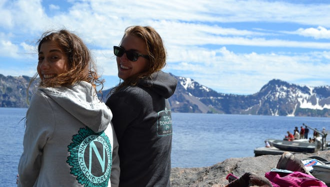 Emilie Hartvig and Alisha Roemeling sit on a large rock at the edge of Crater Lake overlooking the water.
