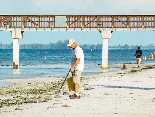 In this file photo, a worker for the town of Fort Myers Beach picks up litter near the pier.