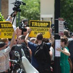 Anti-Trump demonstrators hold signs in front of the media after a meeting between U.S. Senate Republicans and U.S. Republican presidential candidate Donald Trump at the National Republican Senatorial Committee (NRSC) headquarters on July 7, 2016, in Washington, D.C.