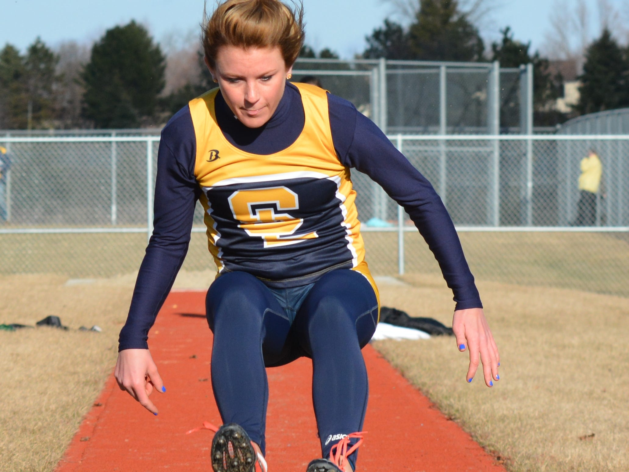 South Lyon's Carlie Fernandez lands her high jump attempt in the opening meet against Novi.