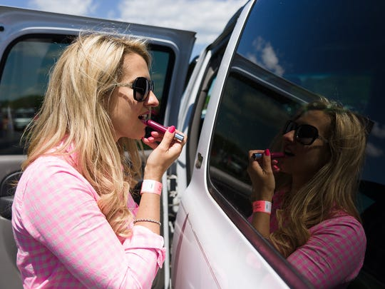 Liz Nygard of Wilmington touches up her lipstick using the reflection of a window as a mirror at the 38th annual Point to Point at Winterthur last year.