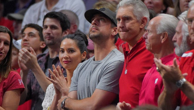 Green Bay Packers quarterback Aaron Rodgers, middle, stands next to actress Olivia Munn as Wisconsin plays North Carolina during the second half of a college basketball regional semifinal in the NCAA Tournament, Thursday, March 26, 2015, in Los Angeles.
